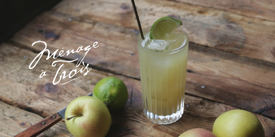 Ménage à trois cocktail with apples and lime on a wooden table
