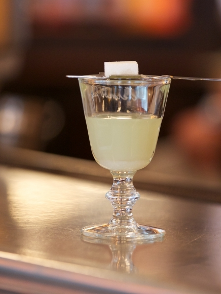 A sugar cube on an absinthe spoon rests on the rim of a glass of Pernod Absinthe