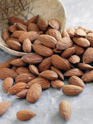 Almonds spill out of small bowl onto grey slate surface