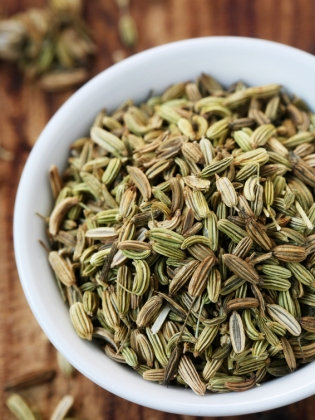 Bowl of fennel seeds on wooden table