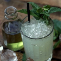 Absinthe Frappé on wooden table with crushed ice