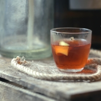 Sazerac cocktail on wooden box with rope and old glass bottle